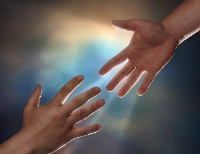 Two male hands; one reaching down to assist another hand reaching up with sunburst in the background